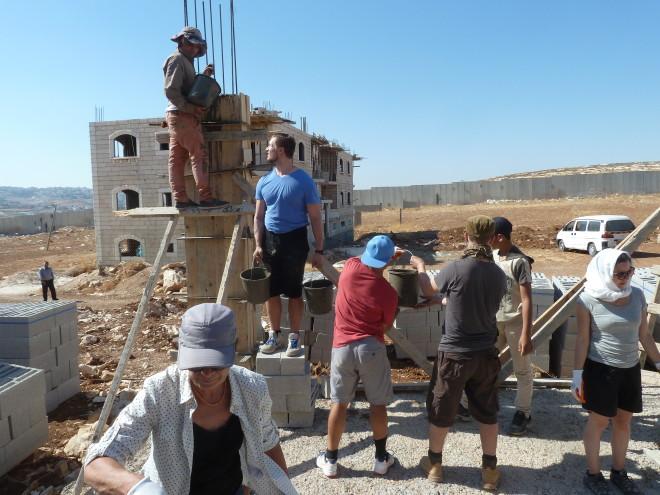 Die Schächte für die 9 Säulen werden mit Beton gefüllt: die Eimer mit dem Mörtel werden von Hand zu Hand weitergereicht.