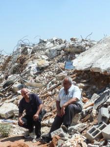 Bewohner von Dahmash vor den zerstörten Häusern
